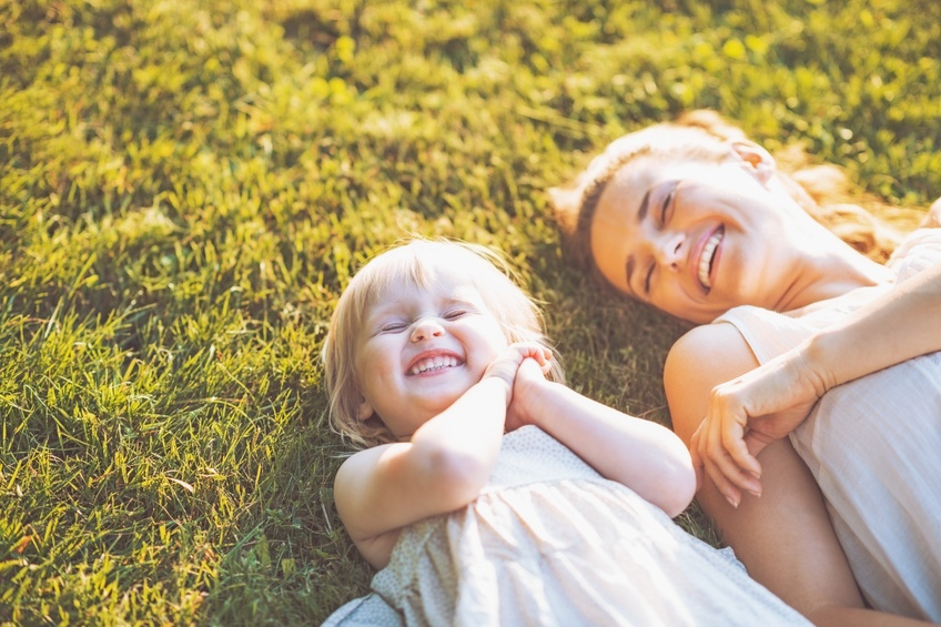 Mother and Daughter Smiling and Laying on Grass