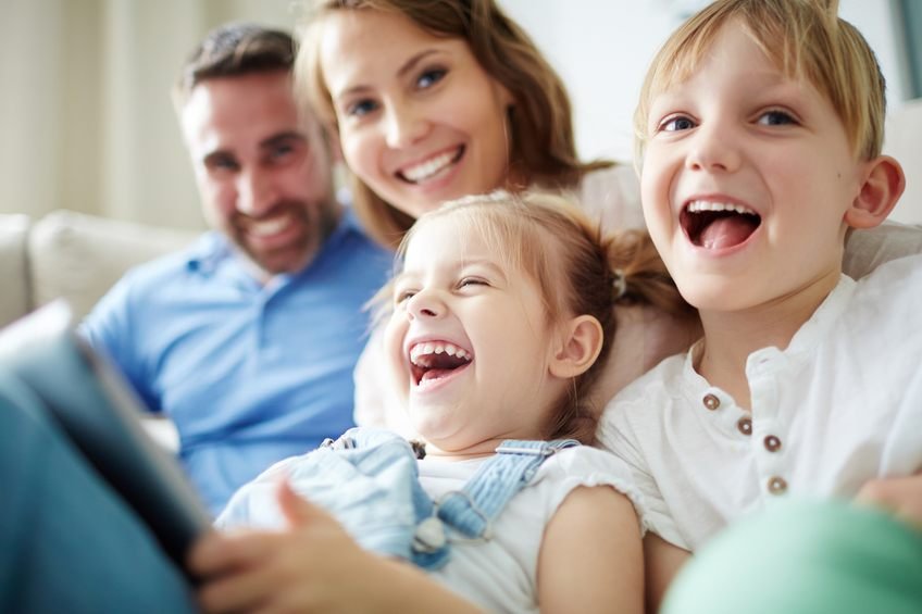 Family Laughing and Embracing on Couch