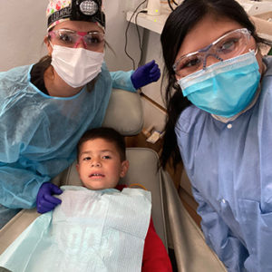 Patty and assistant posing with child in dentist chair