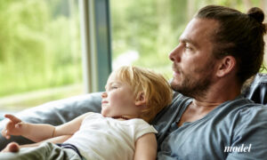Dad and Toddler Looking Out Glass Window