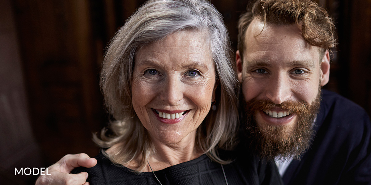 Mother & Older Son Smiling Next To Each Other