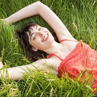 Smiling Young Woman Lying On the Grass
